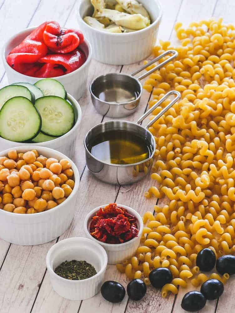 Ingredients to make vegan pasta salad in small prep bowls with uncooked pasta