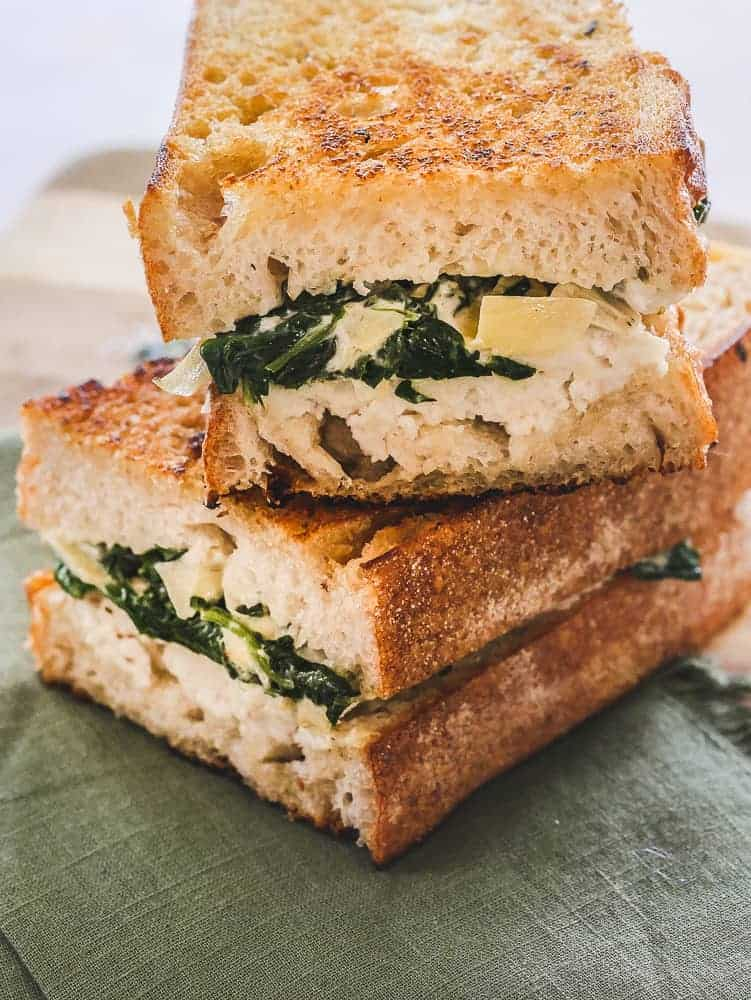 Vegan sandwich with spinach and artichoke chunks, resting on a green napkin