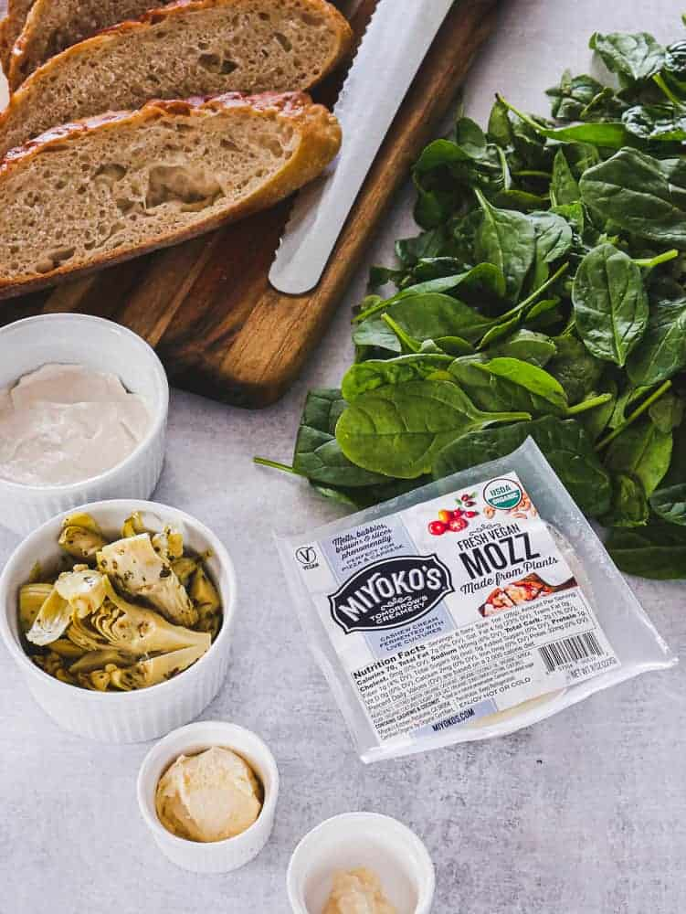 Sandwich ingredients: sliced bread on a cutting board, spinach leaves, artichokes in a bowl