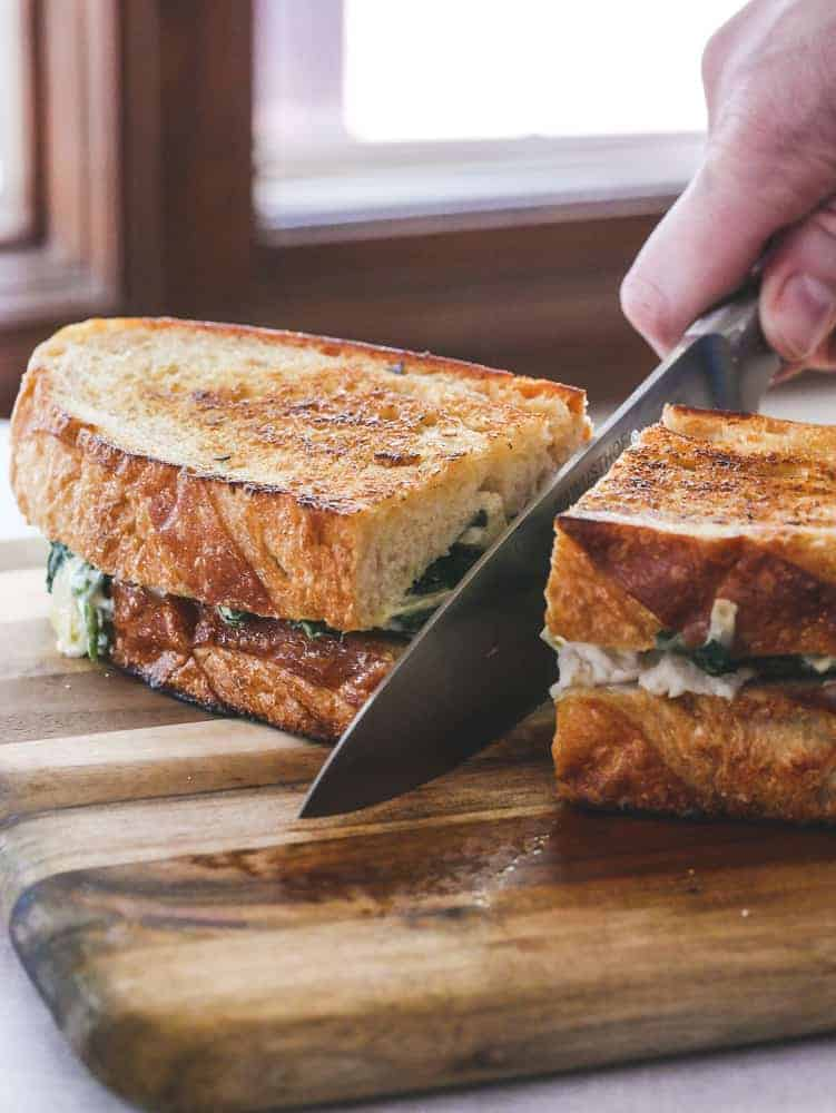 Hand using a knife to cut a grilled sandwich in half on a cutting board
