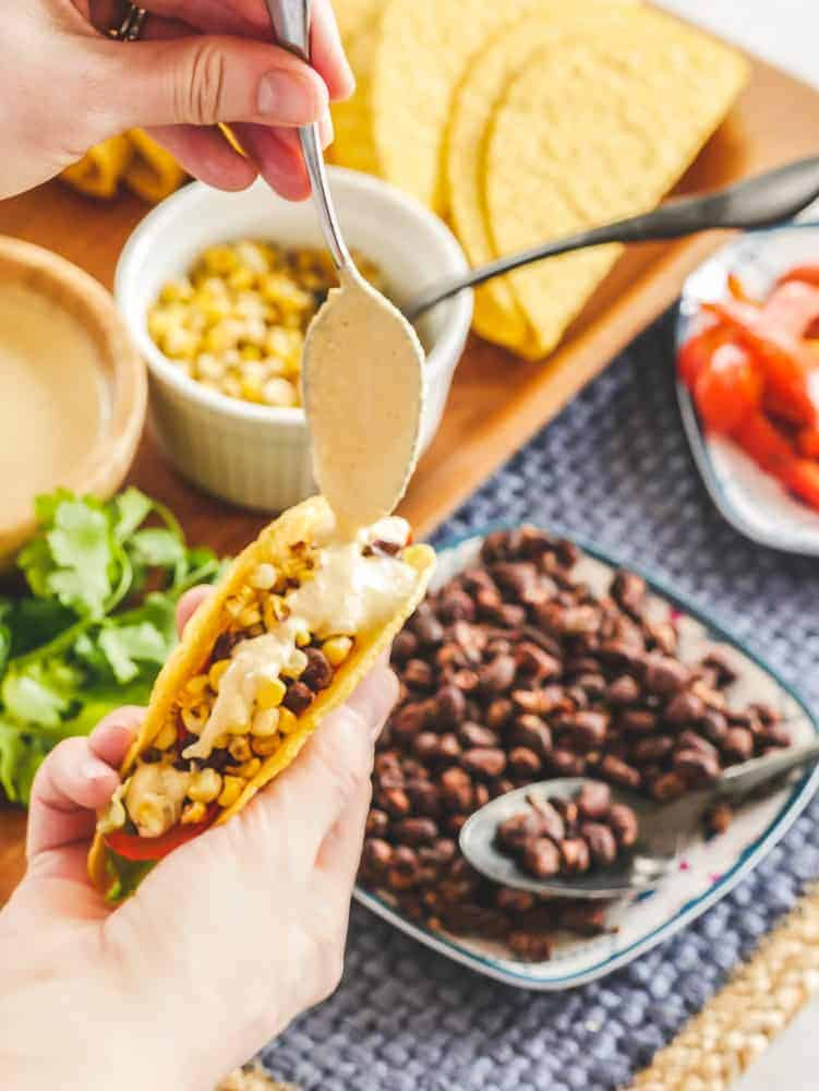 Hand holding a taco shell with taco ingredients in the background