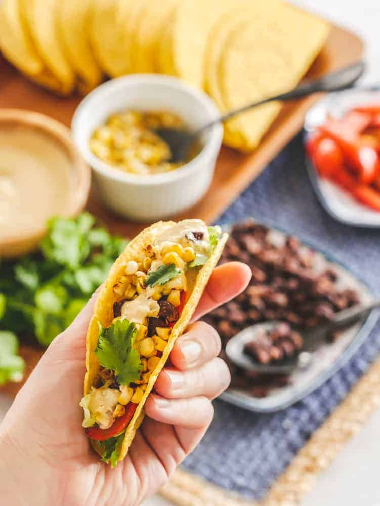 hand holding a vegan taco above a table of taco toppings in bowls
