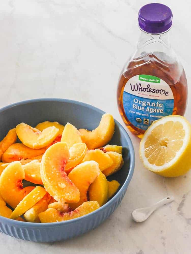 Frozen peach slices in a blue bowl with agave, a sliced lemon and sea salt