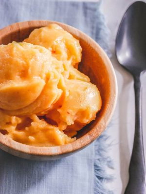 Peach sorbet scoops in a wooden bowl with spoon