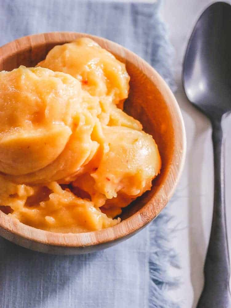 Peach sorbet recipe with frozen scoops in a wooden bowl with spoon