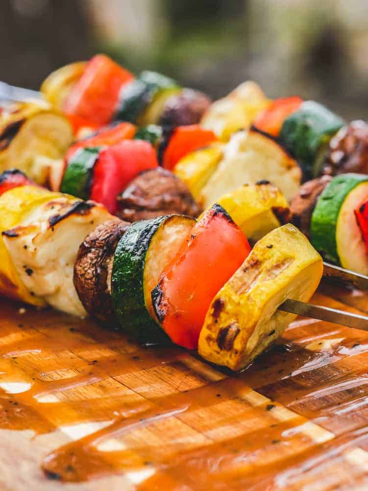 halloumi kebabs and vegetable skewers resting on a cutting board with sauce