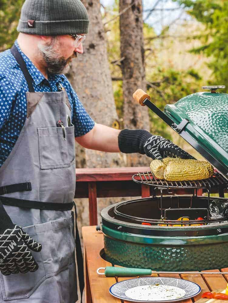 Man with oven mitts turning corn on a green grill