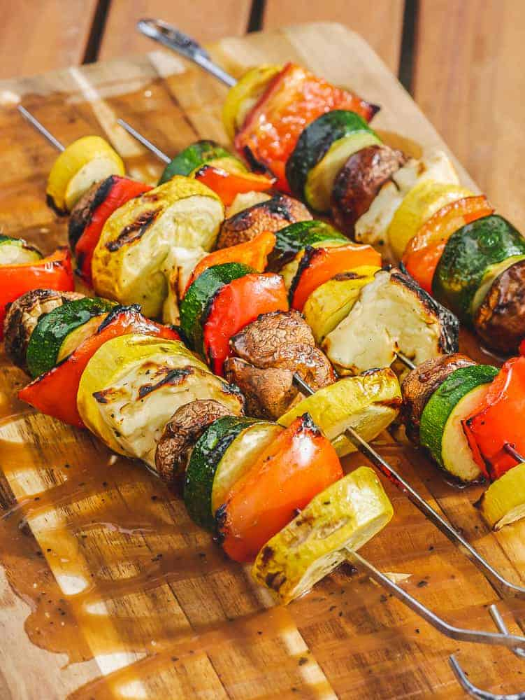 grilled halloumi kebabs and veggies on a cutting board