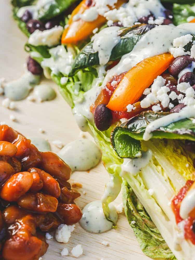 Closeup of a grilled romaine taco salad, with creamy salad dressing. A small pile of baked beans on the side.