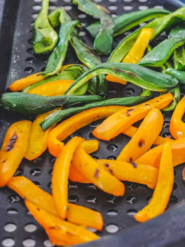 orange and green pepper slices on a grill