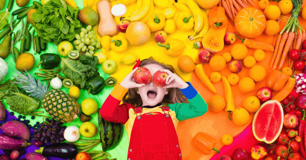 Small child surrounded by colorful fruits and vegetables