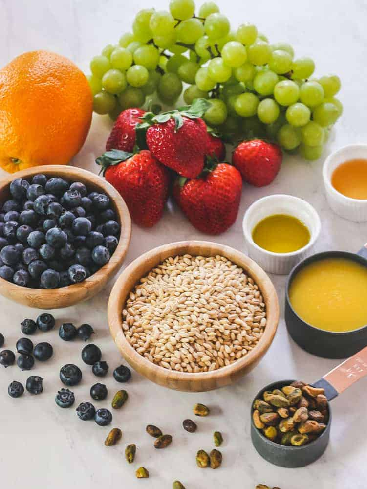 Whole, fresh fruit and barley grains on a white background