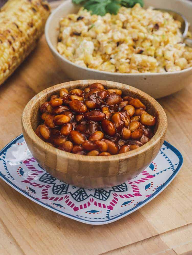 Vegan BBQ beans in a bowl, with grilled corn dishes in the background