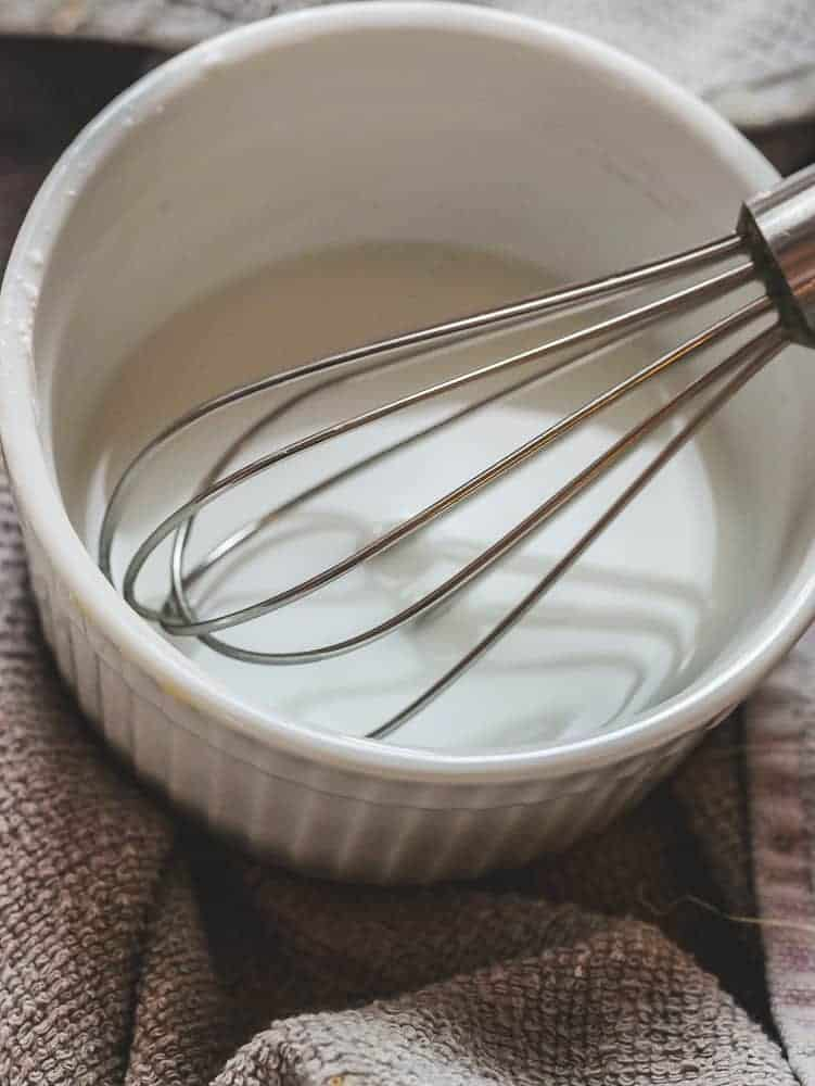 White bowl on a grey towel with a metal whisk