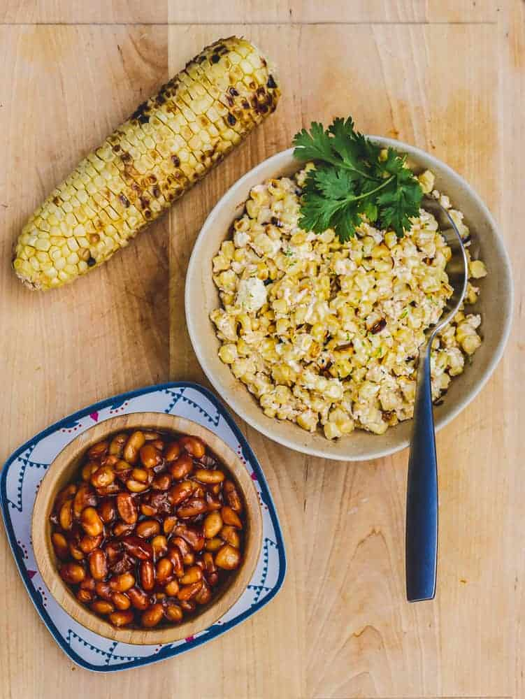 Wooden cutting board with bowl of vegan BBQ beans and grilled corn.