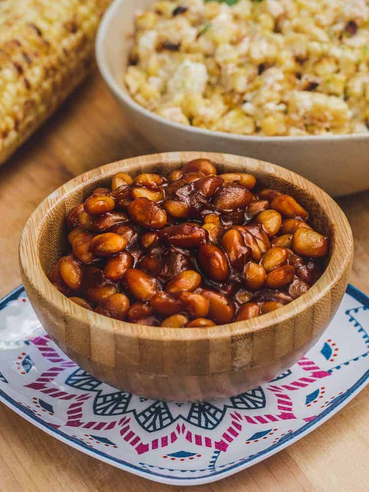 Wooden bowl with vegan bbq beans on a platter with grilled corn and corn salad