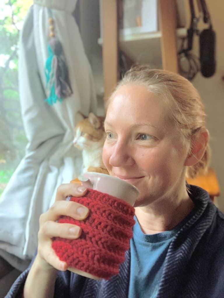 person holding tea cup with cat in background