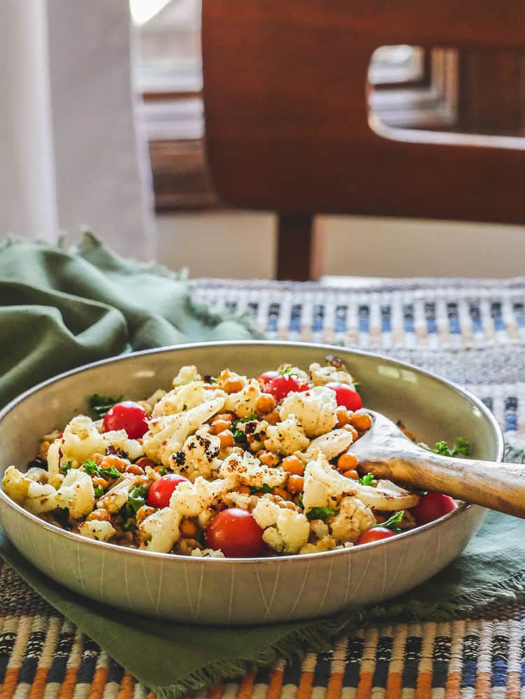 Ceramic bowl of cauliflower, cherry tomatoes and chickpeas resting on a table