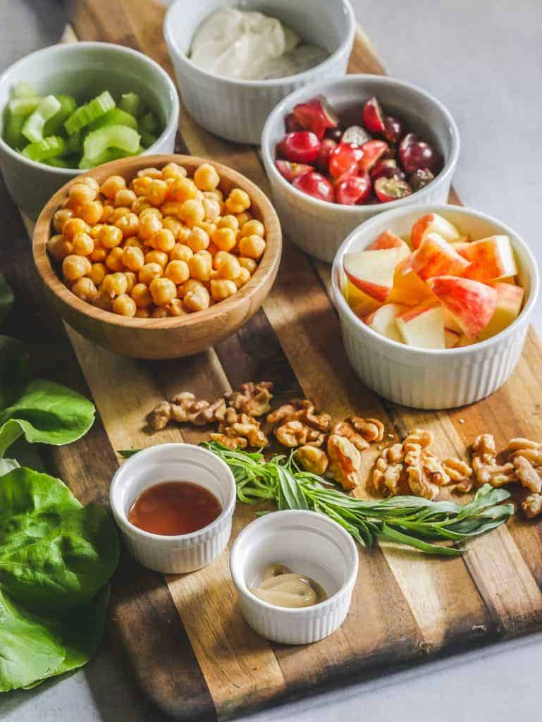 Ingredients to make Chickpea Waldorf salad in small prep bowls, resting on a cutting board.