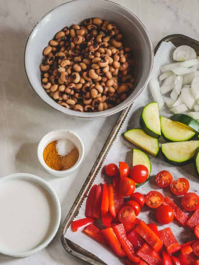 Black eyed peas in a bowl, with chopped vegetables on the side. Small bowls of spices and coconut milk.