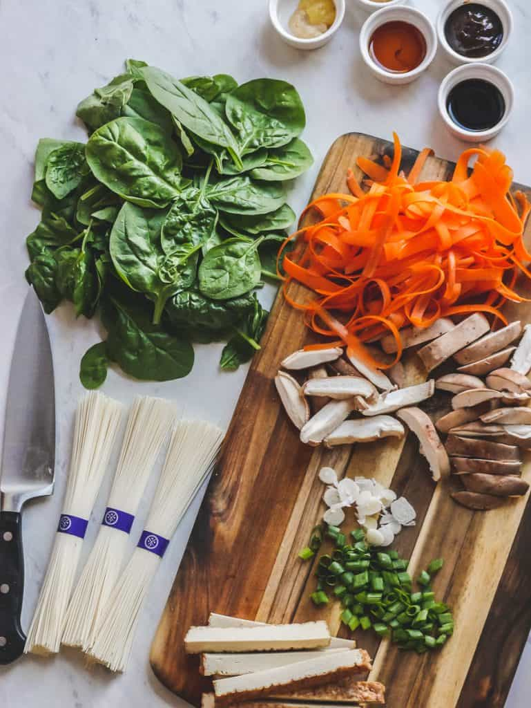 Marble counter and wooden cutting board with fresh vegetables, noodles and a chef knife