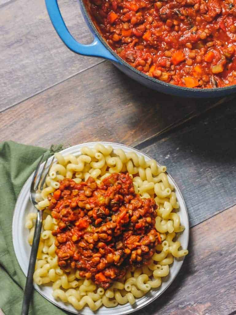 Vegan lentil bolognese scooped on top of cooked pasta, with a fork and green linen napkin on the side.