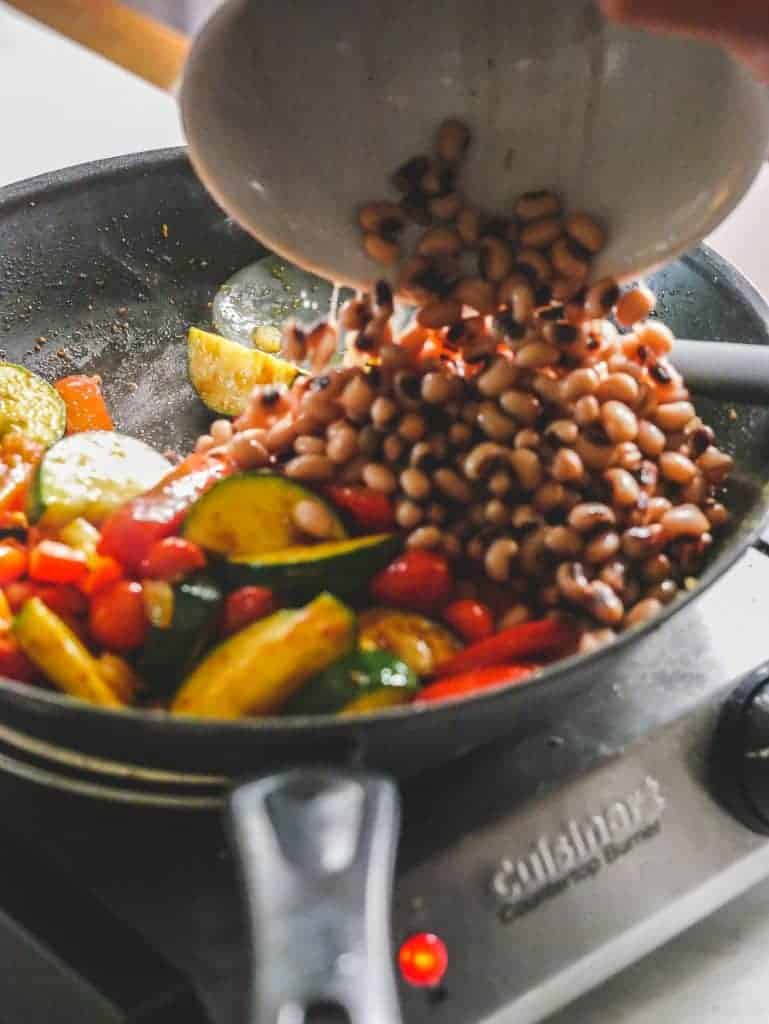 Hand pouring black eyed peas from a bowl into a hot pan