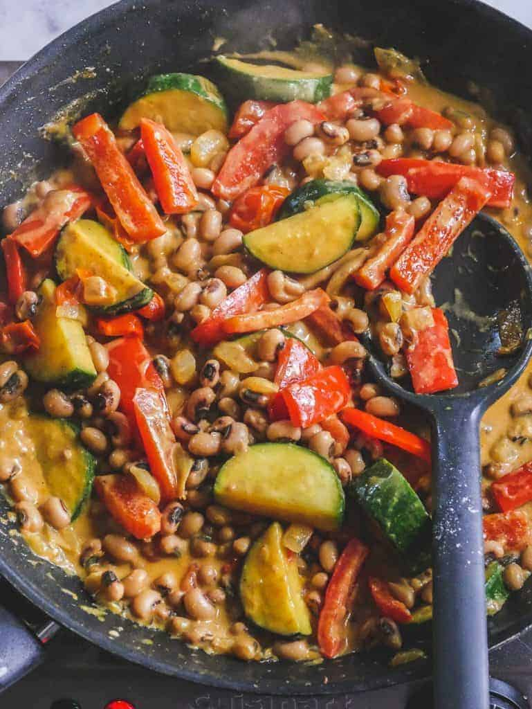 Curried black eyed peas recipe cooking in a large skillet with a spoon resting on the side.