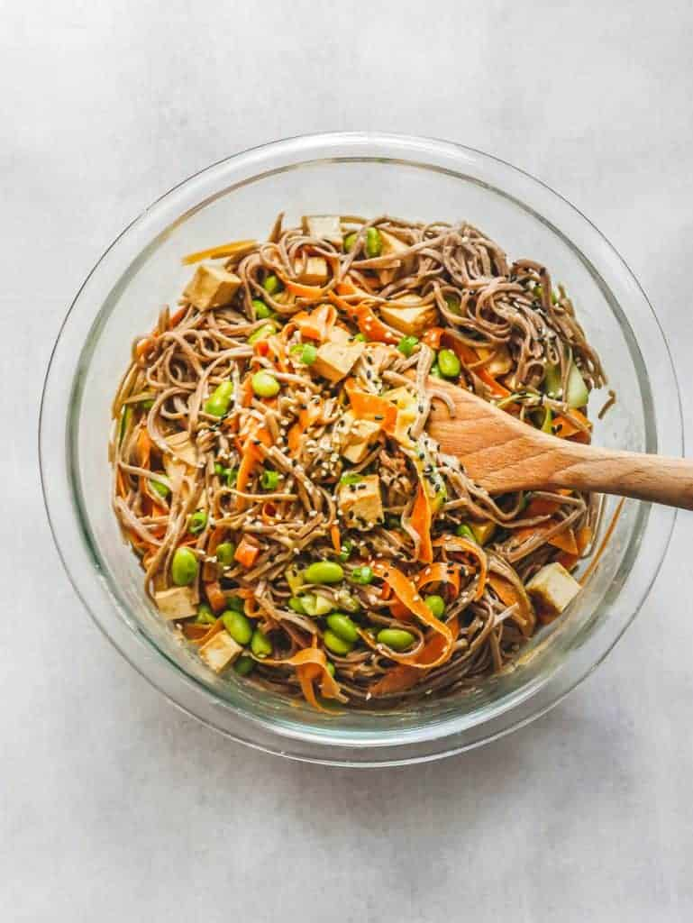 Soba Noodle Bowl in glass bowl with wooden spoon, sesame seeds sprinkled on top