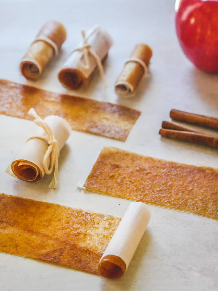 Photograph of homemade fruit leather in various stages of rolling