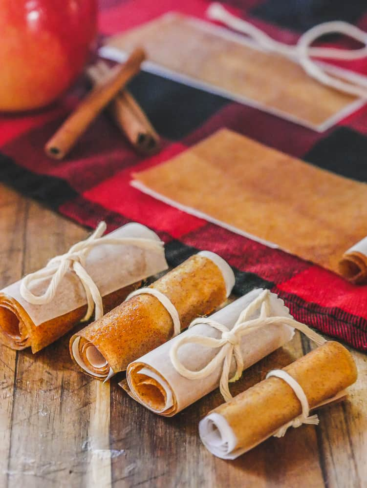 Homemade Fruit Leather roll ups tied with string on a red napkin with apple in the background