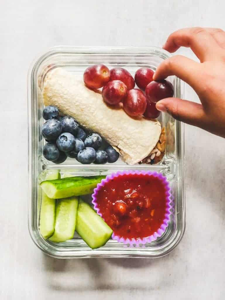 child's hand picking grapes from a lunch box. burrito, blueberries, cucumber and salsa.