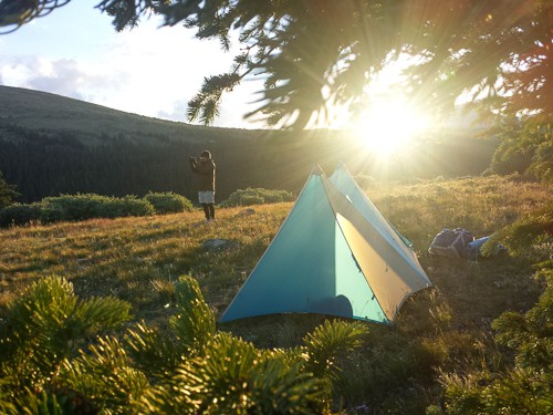 Blue tent at sunset on a mountainside
