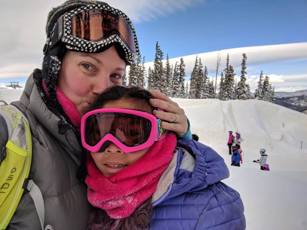 Parent and child wearing ski goggles on a snowy mountain