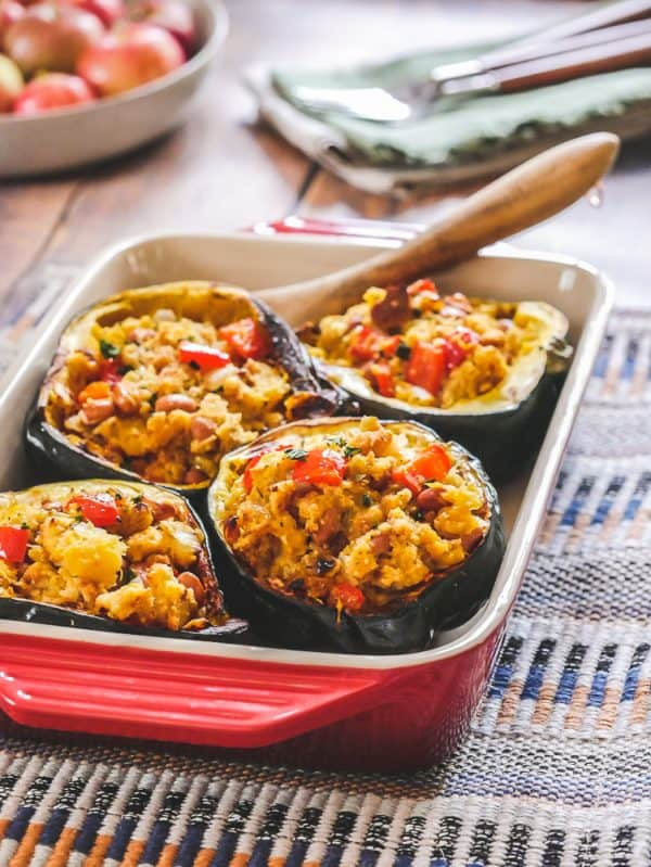 Stuffed acorn squash in a red casserole dish at a holiday table