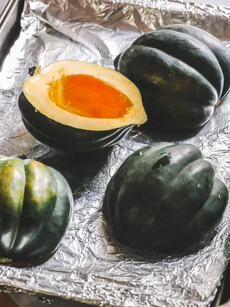 halved acorn squash face down on a foil pan
