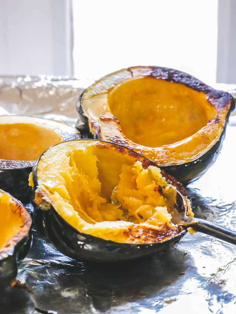 roasted acorn squash halves with a spoon scooping out the insides