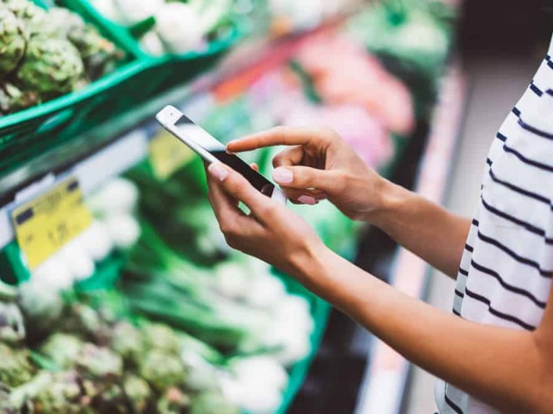 Young woman shopping purchase healthy food in supermarket blur background. Close up view girl blogger buy products using smartphone in store. Hipster at grocery using smartphone. Person comparing price